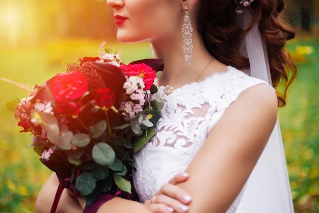 Retrato de noiva com um buquê de flores no parque, dia de sol