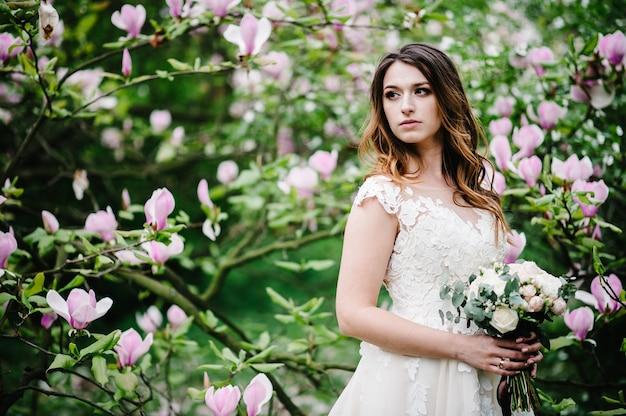 Retrato de noiva com um buquê de pé na natureza de flores roxas de magnólia e verdes.