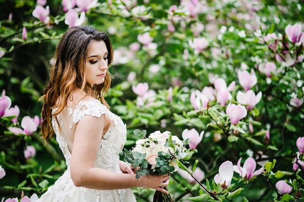 Retrato de noiva com um buquê de pé sobre a natureza de flores roxas de magnólia e verdes.