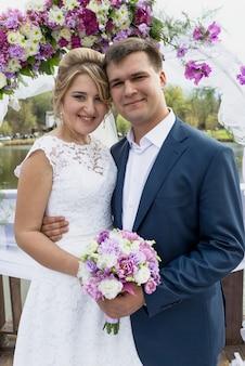 Retrato de noiva e noivo românticos felizes se abraçando na cerimônia de casamento