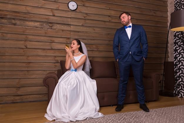 Retrato de noiva fazendo maquiagem e noivo malvado esperando na sala de madeira