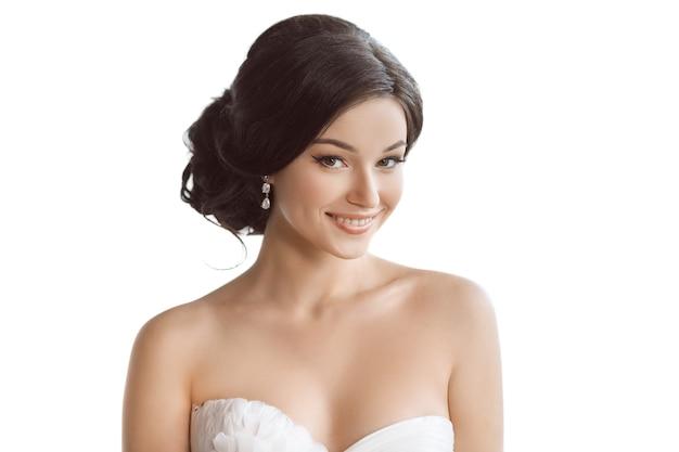 Retrato de noiva jovem beleza com estilo penteado e maquiagem isolado no fundo branco do estúdio.