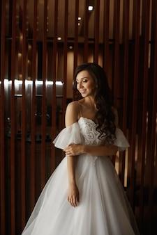 Retrato de noiva jovem de beleza deslumbrante. linda noiva com joias e maquiagem de casamento. modelo de moda nupcial com olhos azuis, posando no interior.