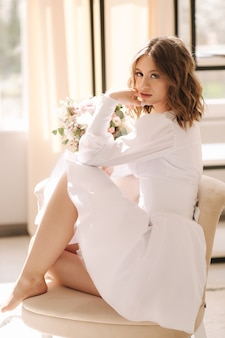 Retrato de noiva linda em sudio sentada na cadeira perto de mulher elegante posando para