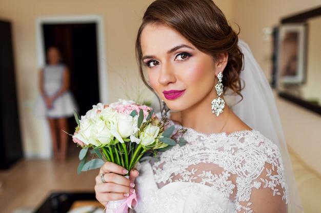 Retrato de noiva linda em vestido de noiva branco brilhante compõem.