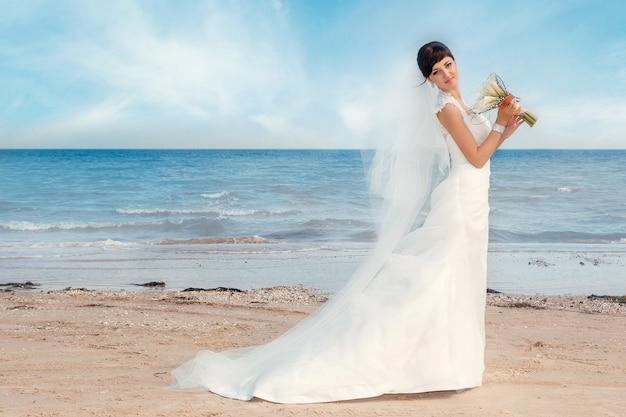 Retrato de noiva linda está de pé na praia