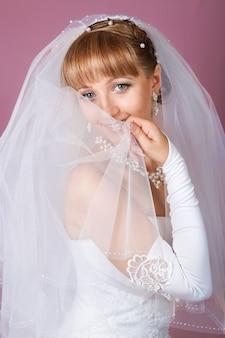 Retrato de noiva linda loira com maquiagem vestindo em branco clássico