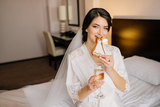 Retrato de noiva no dia do casamento. noiva comendo pão de mel de casamento e segura uma taça de champanhe.