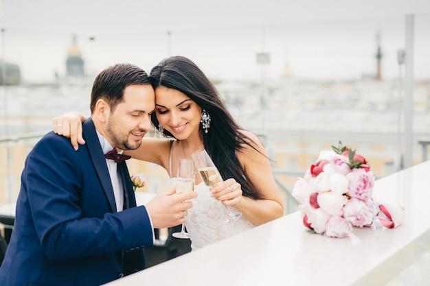 Retrato de noivo barbudo usa terno formal brinca de champanhe com sua esposa