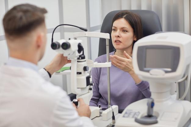 Retrato de oftalmologista masculino usando refratômetro oftálmico durante a consulta