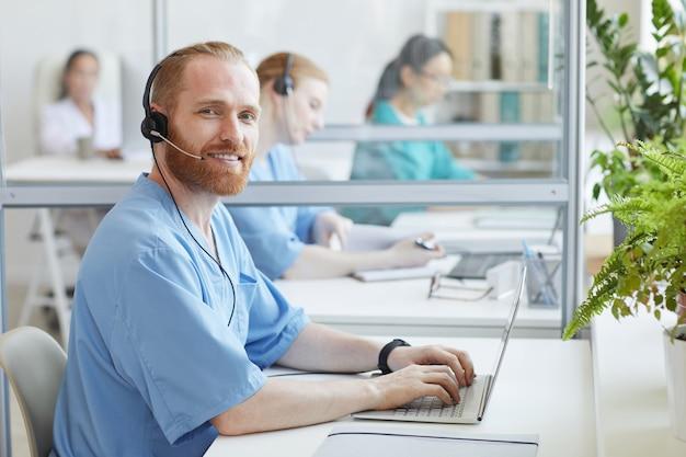 Retrato de operador barbudo em fones de ouvido sorrindo enquanto está sentado à mesa e digitando no laptop no escritório