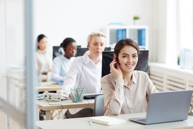 Retrato de operadoras de helpdesk sentadas em fila, com foco na mulher sorridente, olhando enquanto fala com o cliente por meio de fone de ouvido