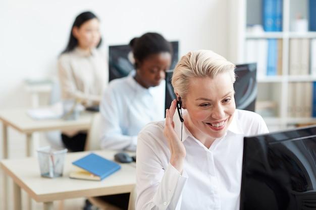 Retrato de operadoras de linha direta femininas sentadas em mesas em uma fileira, foco na mulher sorridente, falando com o cliente por meio de fone de ouvido