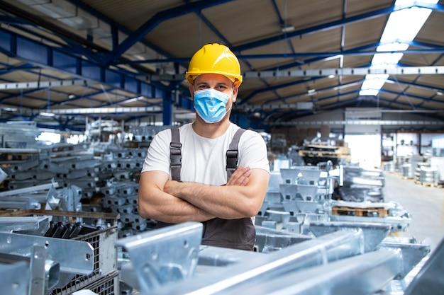 Retrato de operário de fábrica de uniforme e capacete usando máscara facial em uma planta de produção industrial