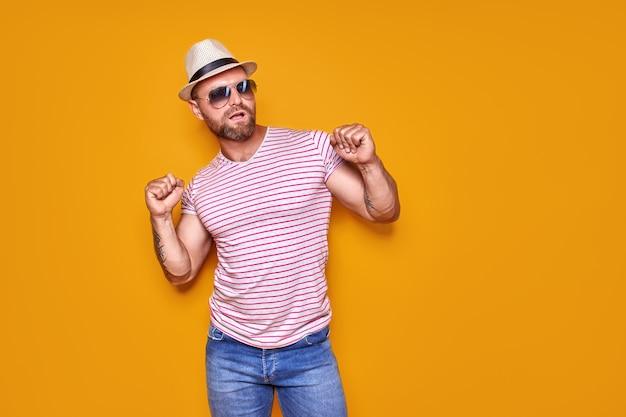 Retrato de otimista funky guy dança desgaste verão olhar óculos de sol de chapéu de palha isoladas em amarelo colo ...