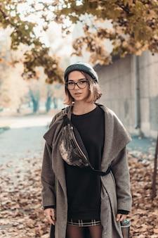 Retrato de outono ao ar livre de jovem, andando na rua da cidade europeia.