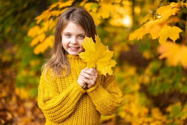 Retrato de outono criança feliz e sorridente segurando nas mãos folhas de bordo amarelo no fundo do outono