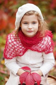 Retrato de outono da menina. menina bonita com folhas de uva vermelhas no outono park. atividades de outono para crianças. dia das bruxas e diversão de tempo de ação de graças para a família.