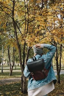 Retrato de outono de estilo de vida na parte de trás da fêmea adulta jovem na floresta ou parque no casaco de chapéu e jeans