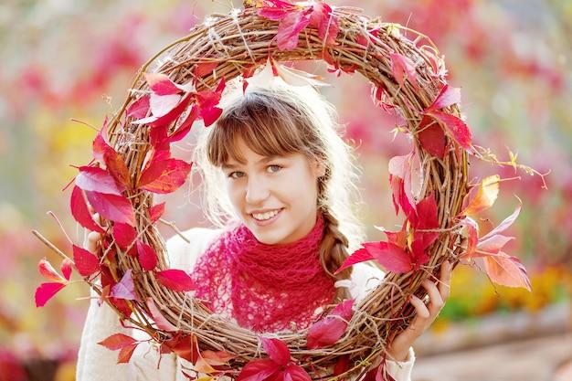 Retrato de outono de menina adolescente. menina bonita adolescente com folhas de uva vermelhas no parque outono.