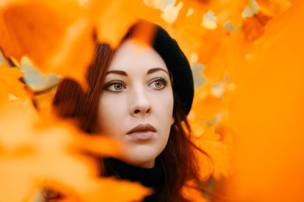 Retrato de outono de mulher ruiva linda garota em uma boina entre as folhas maple park romantic po ...