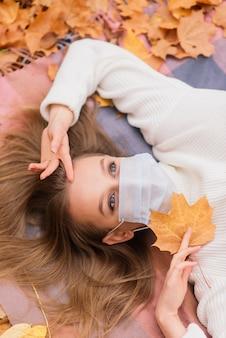 Retrato de outono de uma jovem com uma máscara médica no fundo das folhas amarelas, copie o espaço.