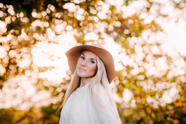 Retrato de outono de uma jovem loira com um chapéu bege e um vestido branco