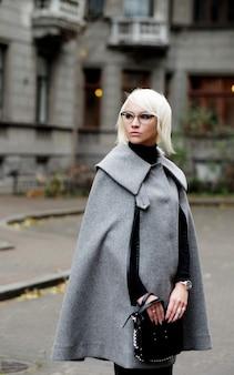 Retrato de outono de uma linda mulher loira com casaco cinza e bolsa preta
