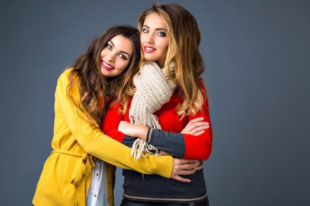 Retrato de outono inverno de moda brilhante, com duas lindas mulheres loiras e morenas, vestindo camisolas e cachecóis elegantes de cores vivas