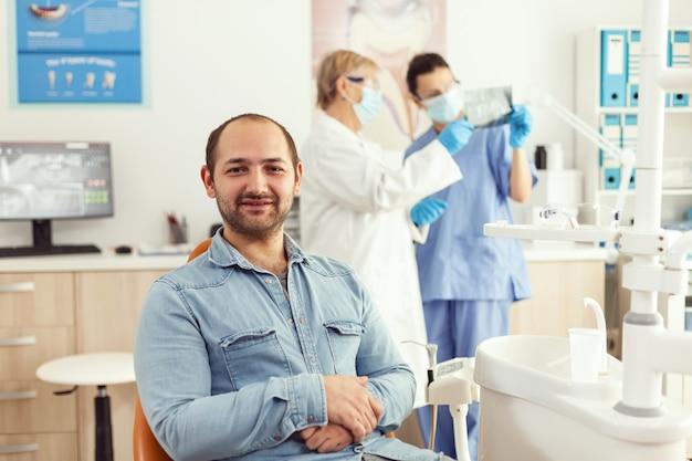 Retrato de paciente homem sentado na cadeira odontológica se preparando para a consulta de estomatologia esperando tratamento de somatologia