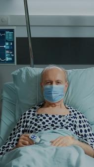 Retrato de paciente idoso com máscara facial sentado na enfermaria do hospital