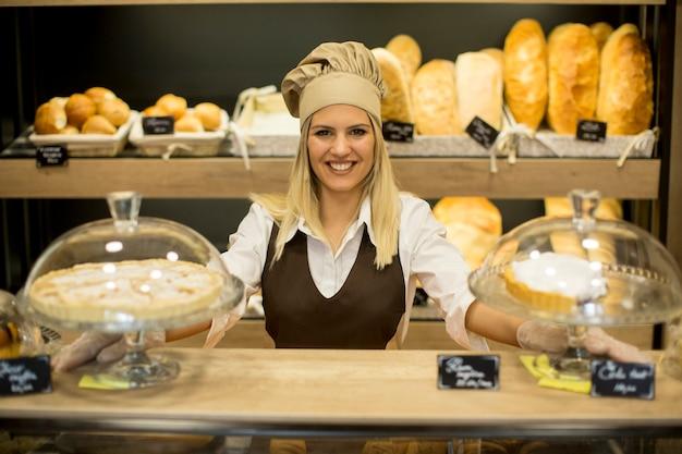 Retrato de padeiro feminino com pão fresco, sorrindo na padaria