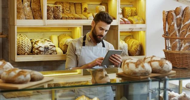 Retrato de padeiro masculino trabalhando na loja de padaria e usando tablet