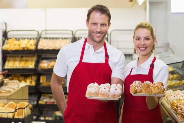 Retrato de padeiros sorridentes com uma pastelaria