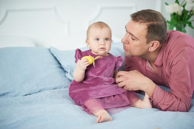 Retrato de pai amoroso brincando com seu bebê de 10 meses de idade no quarto.