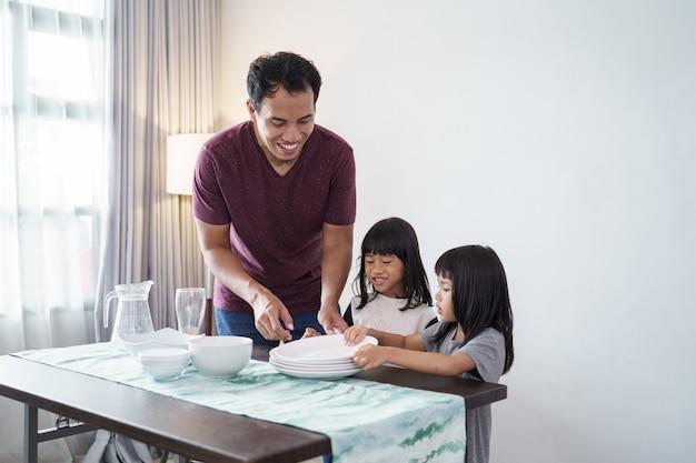 Retrato de pai asiático e filha pequena preparando a mesa de jantar para o jantar