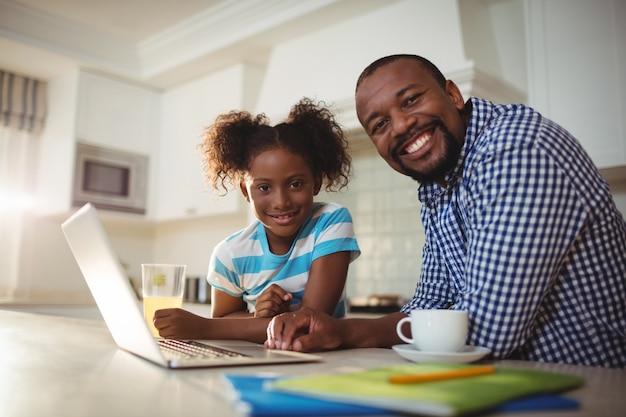 Retrato de pai e filha com laptop