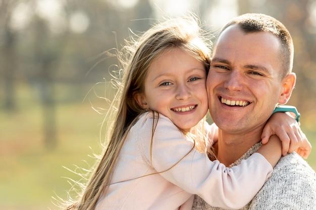 Retrato de pai e filha olhando para o fotógrafo