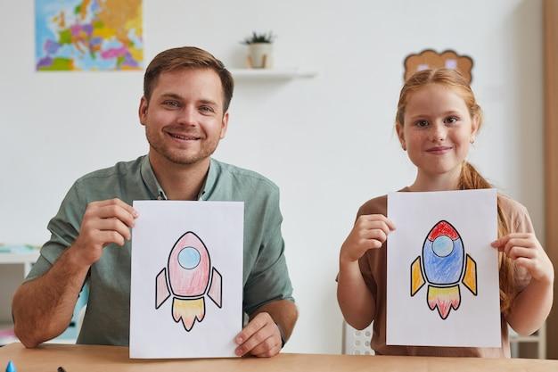 Retrato de pai e filha sorridentes, mostrando fotos de foguetes espaciais enquanto desfrutam da aula de arte na escola ou centro de desenvolvimento juntos