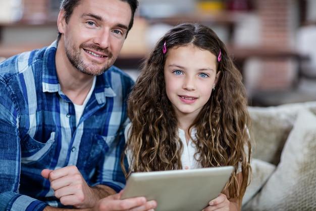 Retrato de pai e filha usando tablet digital na sala de estar
