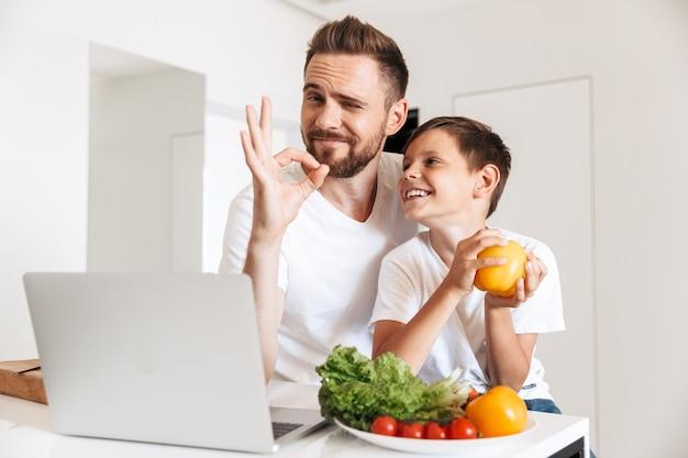 Retrato de pai e filho alegres, sorrindo e usando o laptop para cozinhar a refeição com legumes na cozinha