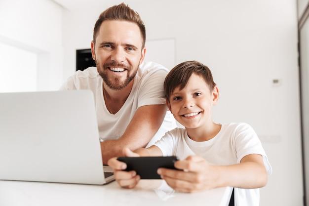 Retrato de pai e filho caucasianos sorrindo juntos em casa, enquanto usam o laptop prateado e jogam no smartphone
