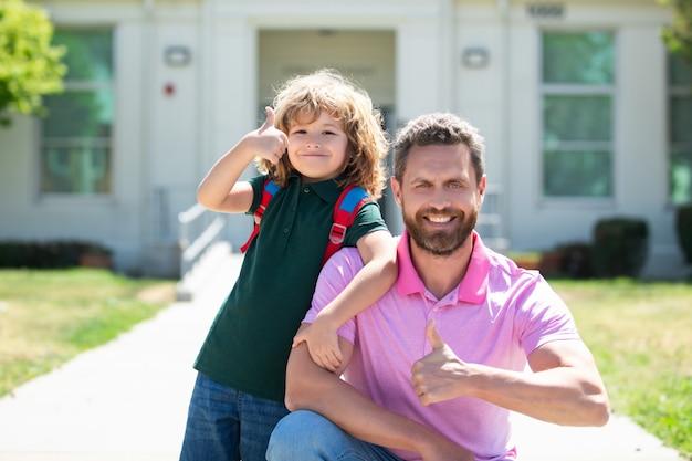 Retrato de pai e filho com polegares para cima perto do parque da escola, de volta às aulas
