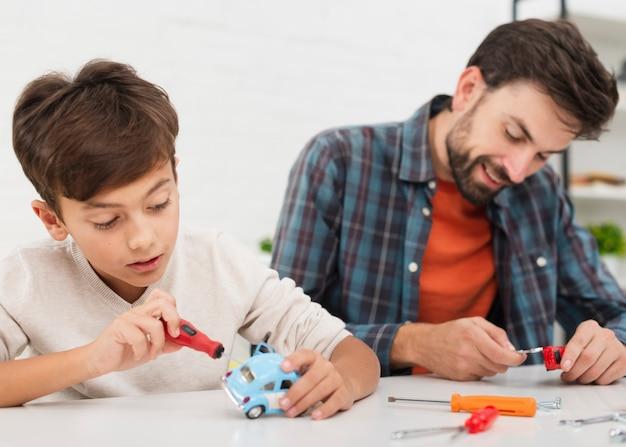 Retrato de pai e filho, consertando carros de brinquedo