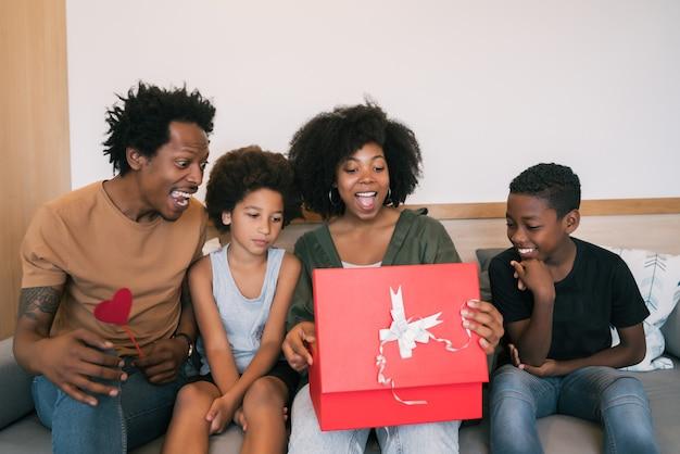 Retrato de pai e filhos parabenizam a mãe no dia das mães e dão presentes em casa. conceito de celebração do dia das mães.