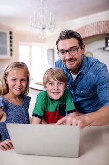 Retrato de pai e filhos usando o laptop na cozinha