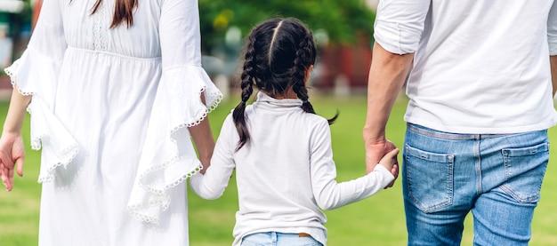 Retrato de pai e mãe de família asiática segurando a mão de uma menina