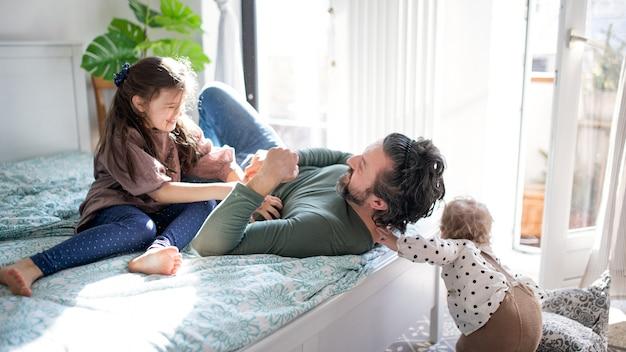 Retrato de pai feliz com duas filhas pequenas se divertindo na cama em casa.