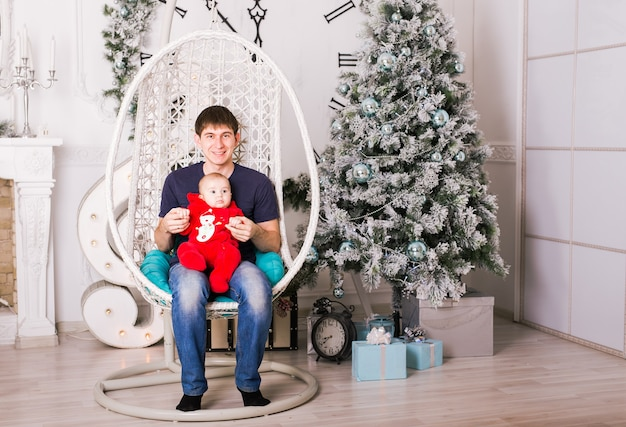 Retrato de pai jovem feliz sentado na cadeira e brincando com seu filho bebê perto de árvore de natal.