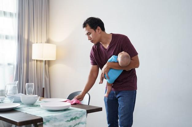 Retrato de pai solteiro fazendo tarefas domésticas enquanto carrega seu filho